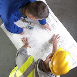 Builders discuss construction blueprint